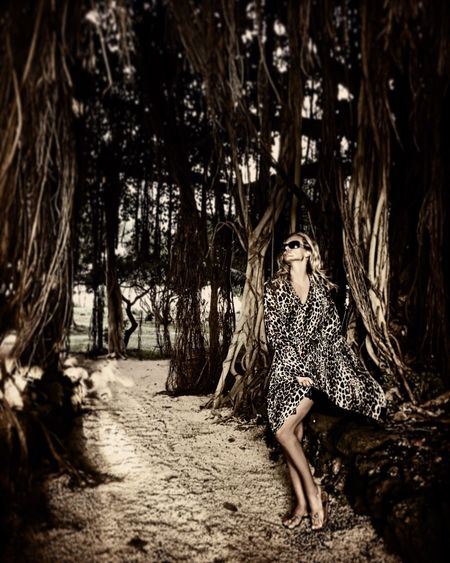 Full length of seductive woman standing amidst trees in forest
