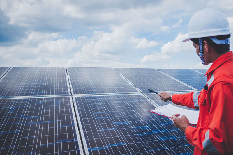Engineer checking solar panel against cloudy sky
