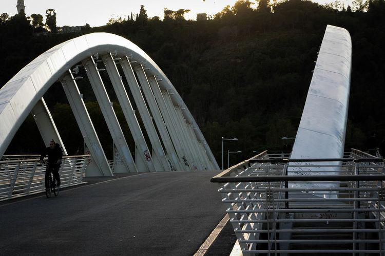 Bridge leading towards road against sky