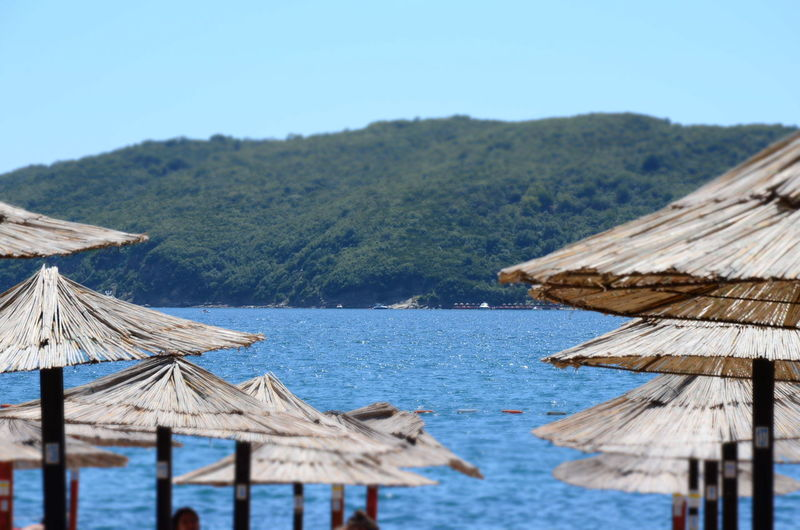 Water Mountain Wood - Material Nature Roof Beauty In Nature Thatched Roof Scenics - Nature Tranquility Focus On Foreground Clear Sky Wood Sea Tranquil Scene ЯПЧерногория Beach Beachphotography Travel EyeEm Gallery Montenegro