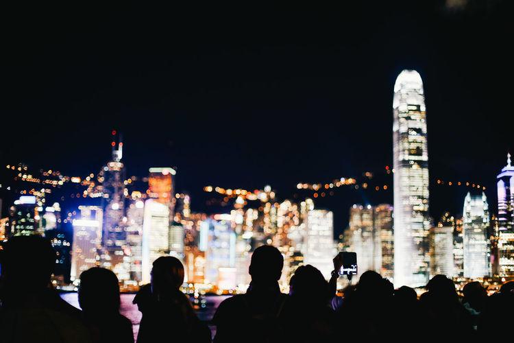 People on illuminated buildings against sky at night