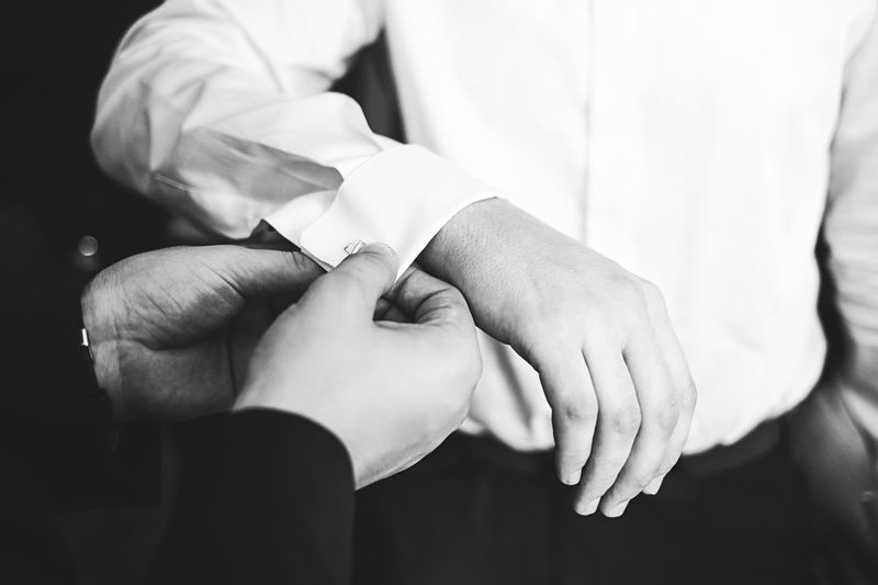 Close-up of male hands adjusting cufflinks of groom
