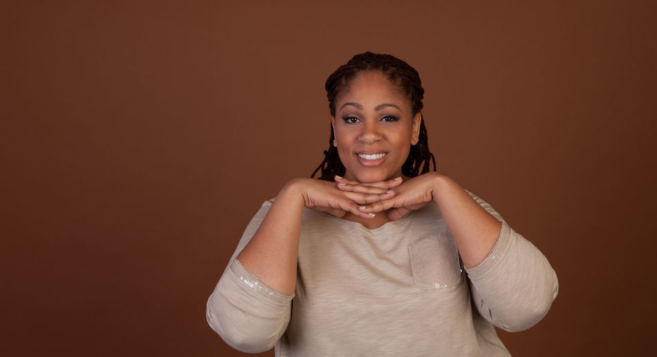 Portrait Of Smiling Overweight Woman Against Brown Background