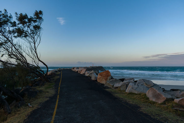 Road by sea against sky during sunset