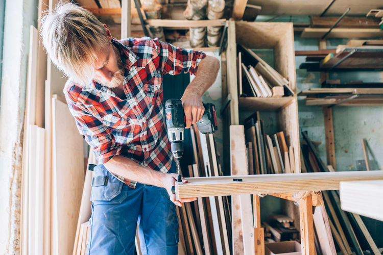 carpenter working with a drill on a wooden table Crafts Hands Industry Workshop Adult Art And Craft Carpenter Carpentry Casual Clothing Craft Creativity Drill Indoors  Jeans Ladder Men Mid Adult Occupation One Person Skill  Standing Three Quarter Length Wood - Material Working Workshop