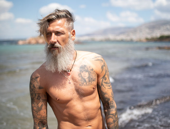 Thoughtful shirtless man with beard standing at beach