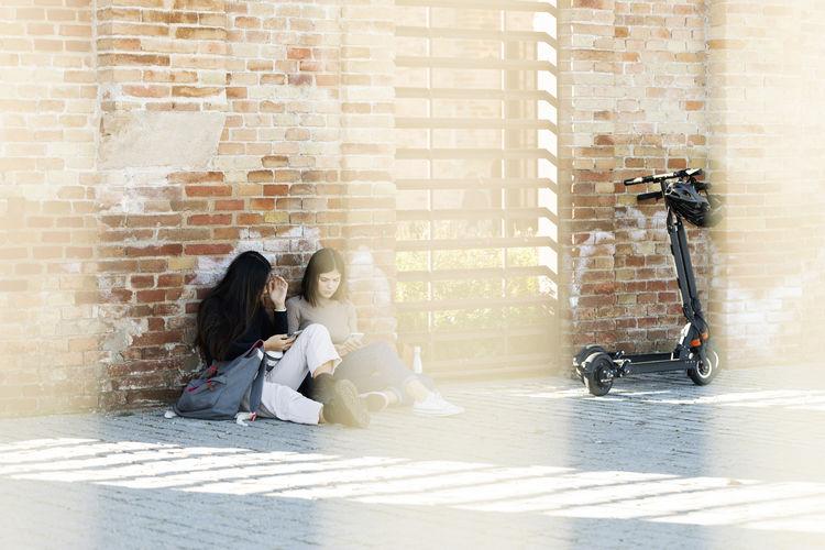 Women sitting against brick wall