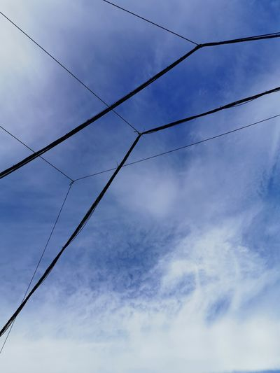 Low angle view of power cables against blue sky