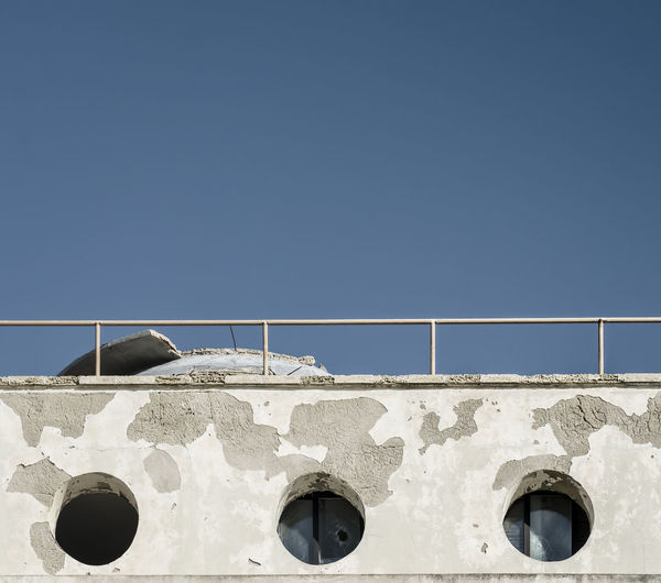 Low Angle View Of Old Abandoned Prison Against Clear Blue Sky