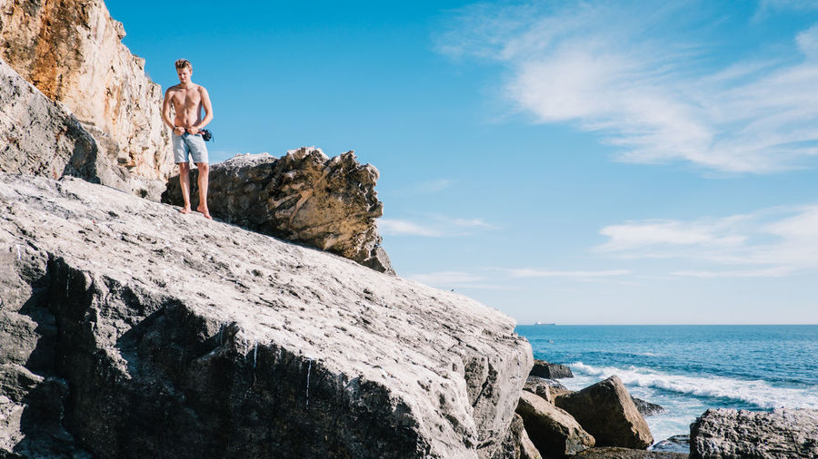 Low Angle View Of Man Standing On Cliff By Sea Against Sky