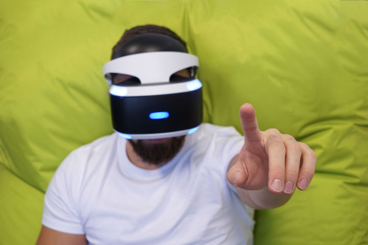 Man gesturing while wearing virtual reality simulator against curtain