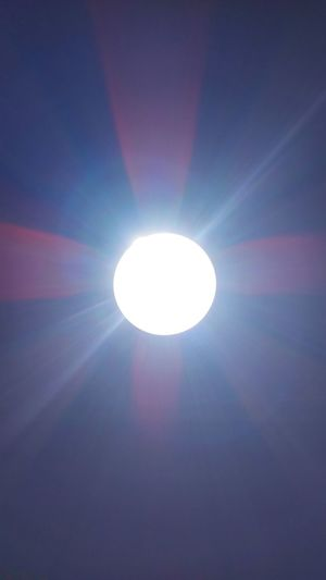Scenic view of bright sun against sky