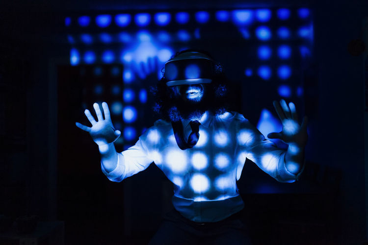 Portrait of young man standing against illuminated blue light
