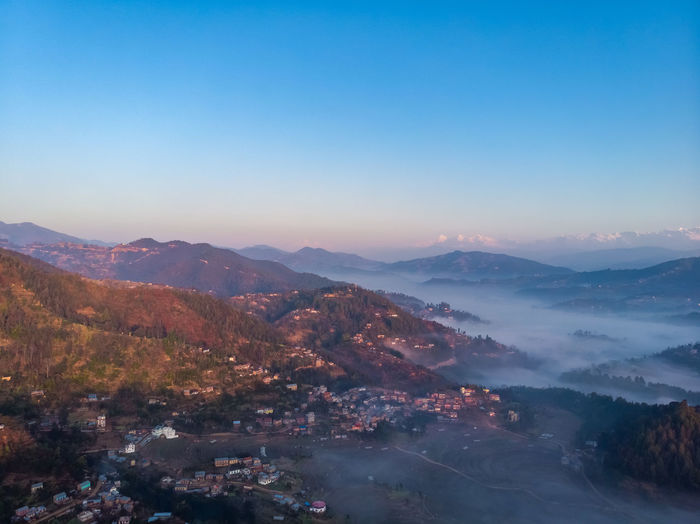 Scenic view of mountains against clear sky during sunrise