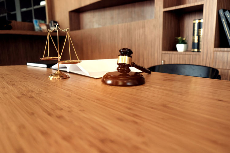 Close-up of gavel and weight scale on table