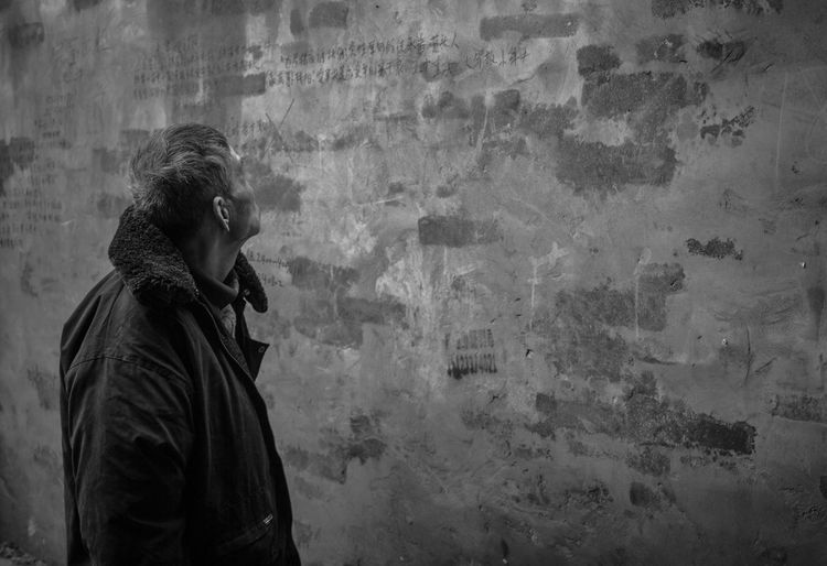 Man looking at damaged wall