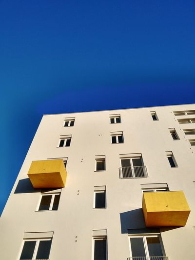 Low angle view of building with yellow balconys against clear blue sky