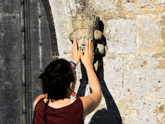 Rear view of women touching sculpture on wall
