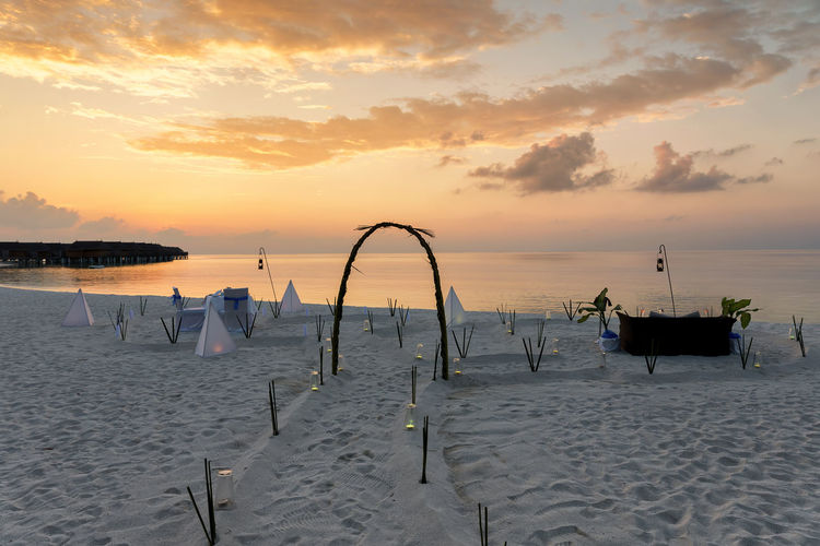 Romantic dinner setup for a honeymoon couple on a tropical beach Couple Exotic Maldives Romantic Travel Vacations Beach Beauty In Nature Cloud - Sky Honeymoon Horizon Over Water Idyllic Island No People Orange Color Private Sand Scenics - Nature Sea Sky Sunset Tranquil Scene Tranquility Tropical Water