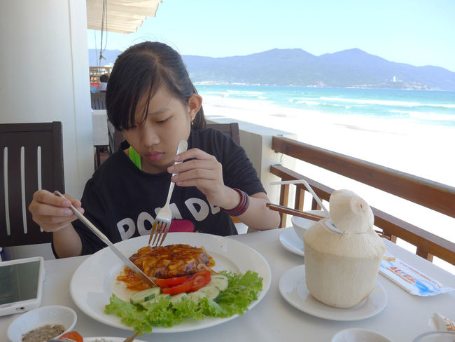 GIrl learning to use knife and fork at beachside restaurant in Da Nang, Vietnam. 4U Restaurant Beaches Children Chopsticks Coconuts Concentration Cutlery Danang Dining Eating Food And Drink Fork Learning Lettuce Ocean Restaurants Salad Sea Steak Table Vietnam Views White Sand