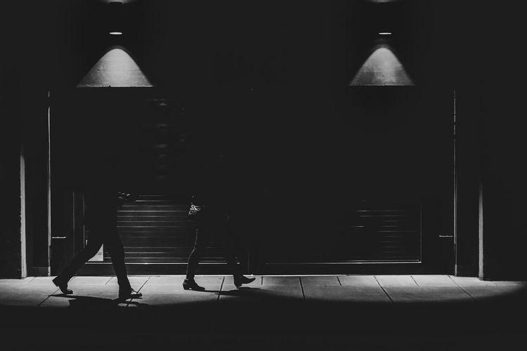Rear view of people walking on footpath in building