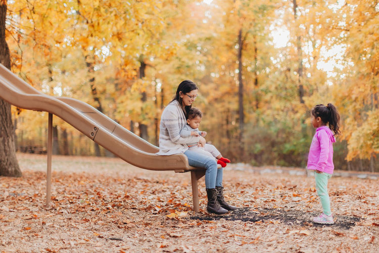 Mother and kids playing in park during autumn