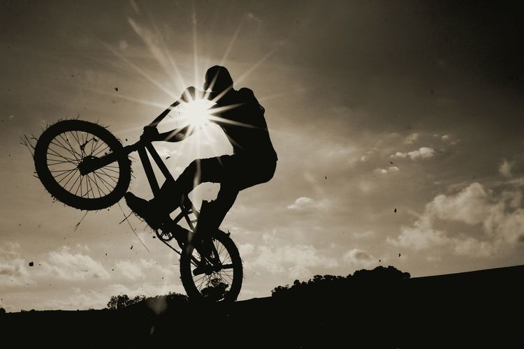 Low angle view of man performing stunt with bicycle against sky during sunset