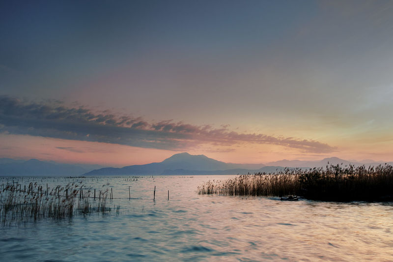 Beauty In Nature Cloud - Sky Idyllic Lugana Mountain Nature No People Non-urban Scene Orange Color Outdoors Remote Scenics - Nature Sea Sky Sunset Tranquil Scene Tranquility Water Waterfront Wooden Post