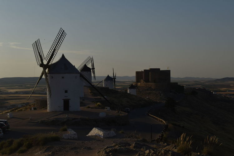 Traditional windmill on land against sky during sunset