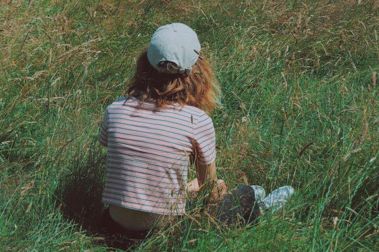 Rear view of girl sitting on grassy field