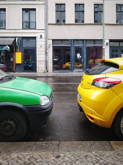 View of yellow car parked on street against buildings