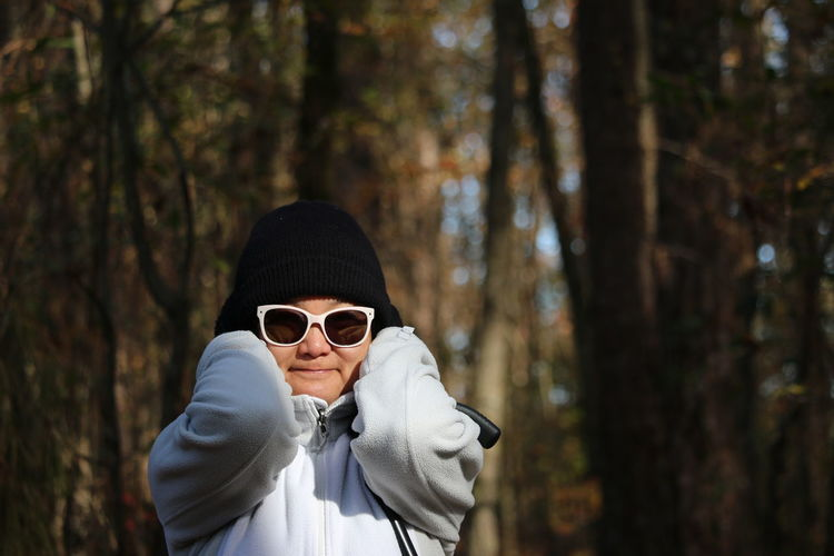 Portrait of woman wearing sunglasses standing in forest