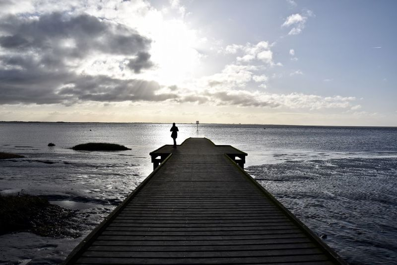Rear view of woman by sea on pier during sunset
