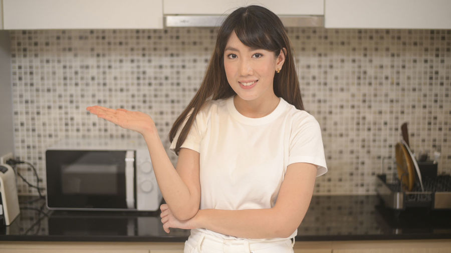 Portrait of smiling young woman standing at home