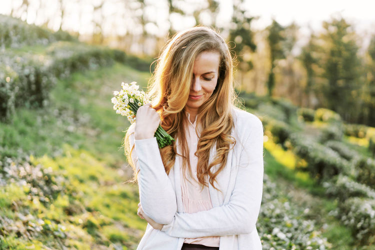 Beautiful young woman standing by flower plants