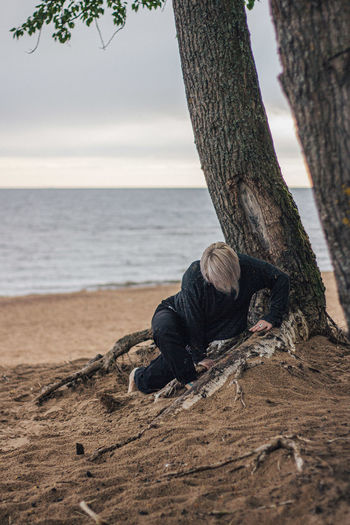 Man on tree trunk by sea against sky