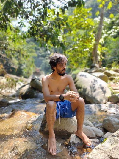 Full length of shirtless man sitting on rock