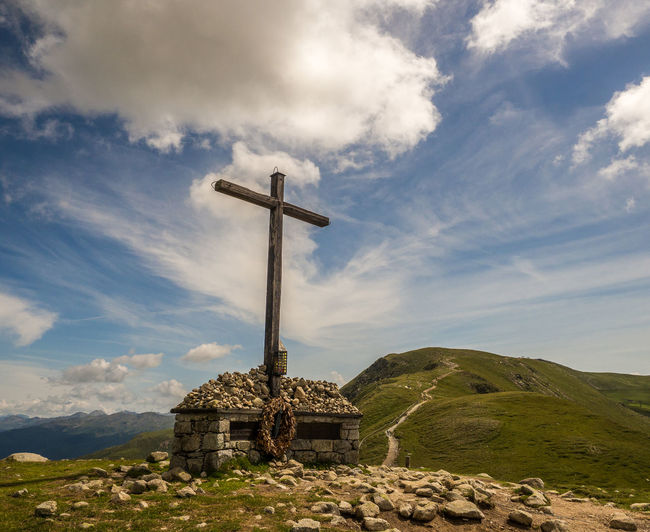 Cross on cliff against sky at alto adige