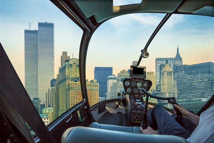 Helicopter cockpit flies in New York City with World Trade Center and Twin Towers, Manhattan, United States, with pilot arm and control board inside the cabin. Helicopter View  Helicopter Cockpit Flight Aerial View Flying United States America Cabin Window Skyline Cityscape New York City WTC Twin Towers Built Structure Architecture Building Exterior Office Building Exterior Sky Glass - Material Transparent Skyscraper Building Urban Skyline Landscape Vehicle Interior Tall - High Travel Office Transportation Nature Day Modern Outdoors Financial District
