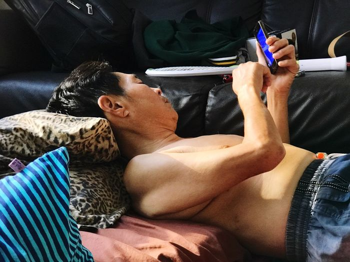 Mature man using mobile phone while resting at home