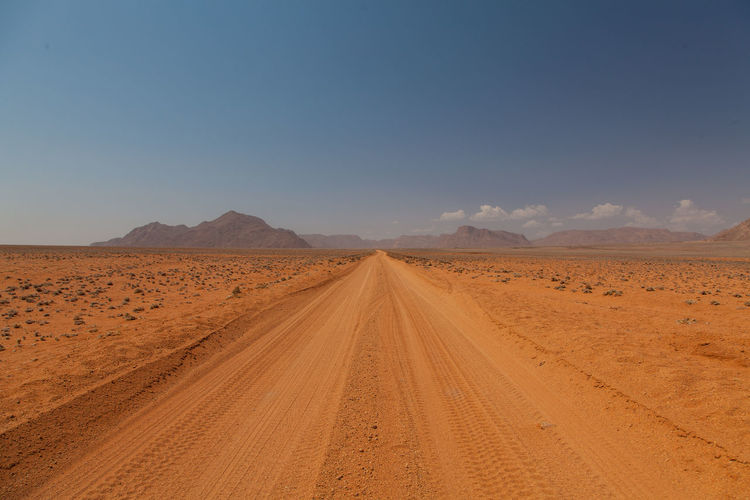 Offroad track namibia Adventure Arid Climate Beauty In Nature Clear Sky Day Desert Environment Horizon Landscape Mountain Namibia Nature No People Offroad Outdoors Road Sand Sand Dune Scenics Sky Sunset The Way Forward Tire Track Travel