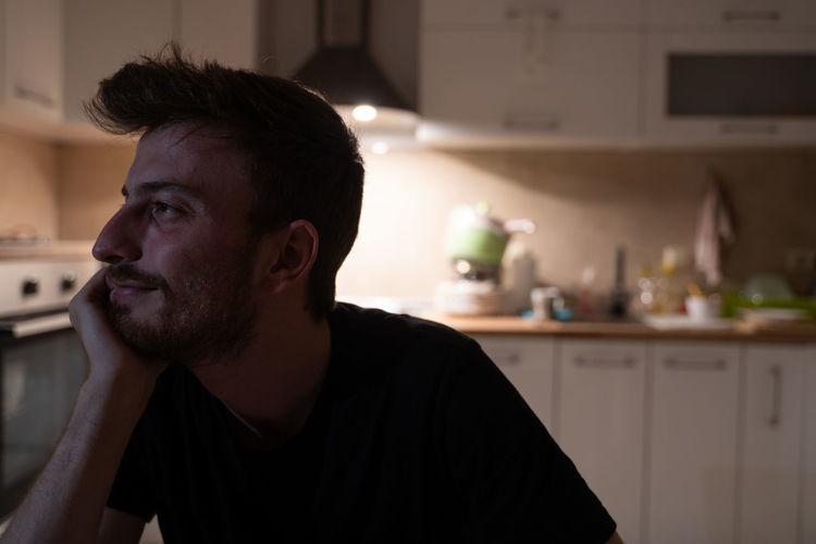 Young european guy pictured in his kitchen, pressing fist to jaw as if dreaming of something.
