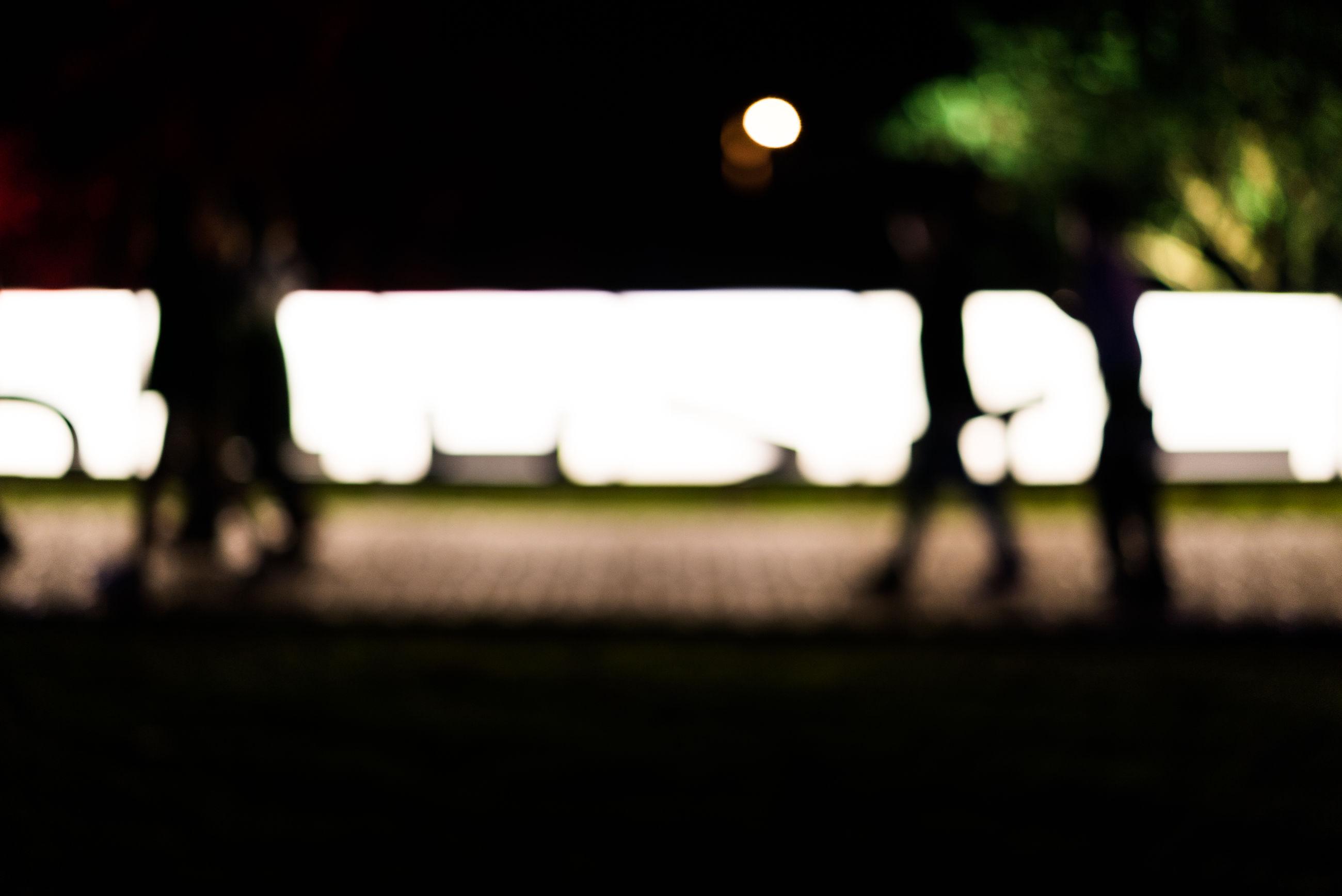 CLOSE-UP OF ILLUMINATED LIGHTING EQUIPMENT ON FIELD AGAINST NIGHT