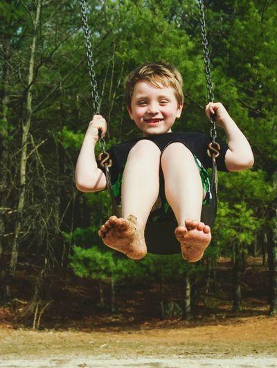 Full length of playful boy swinging in playground