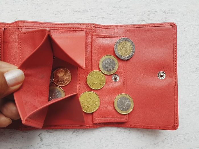 High angle view of coins in red purse