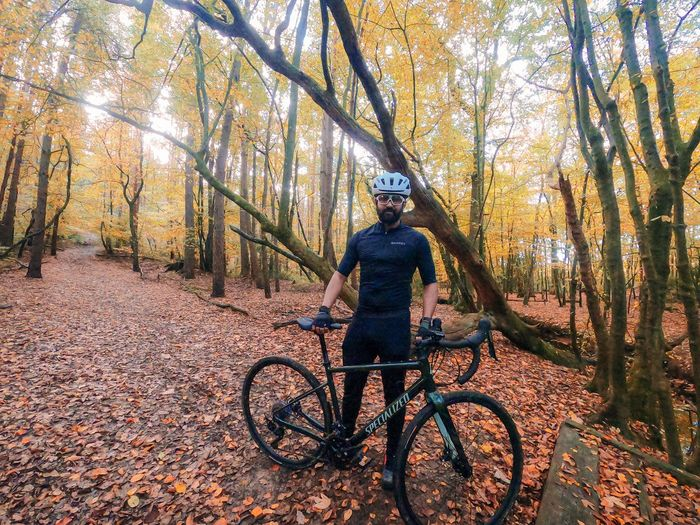 Man riding bicycle on autumn leaves