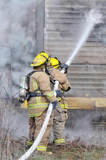 Firefighter Danger Train Fire Fire Hose Firehose Helmet Safety Headwear Fire Hose Protective Workwear Emergency Equipment Smoke - Physical Structure Heroes Uniform Protection Reflective Clothing Outdoors Teamwork Courage Working Rescue Worker Men People Water