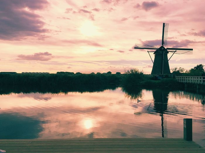 Traditional windmill by lake against cloudy sky during sunset