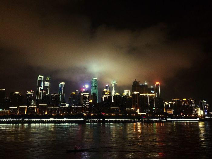 Yangtze river by illuminated cityscape against sky at night