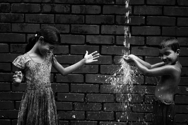 The Street Photographer - 2018 EyeEm Awards Aggression  Brick Brick Wall Casual Clothing Emotion Fun Hair Hairstyle Human Arm Motion Outdoors People Real People Sister Standing Two People Wall Wall - Building Feature Water Women Young Adult Young Women This Is Strength Holiday Moments Human Connection Moments Of Happiness 2018 In One Photograph